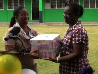 Teacher at the Joycelyn Liburd Primary School Ms. Andie Neale presents Mrs. Evelina Claxton, the school's longest serving teacher with a gift as part of its 35 anniversary celebrations