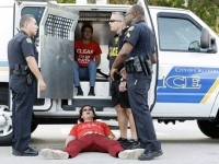 One of 15 immigration reform activists refuses to get up after being arrested by Orlando police for blocking a street intersection Tuesday in Orlando, Florida. A march and rally was to support passage of a pathway-to-citizenship bill for immigration reform. - AP