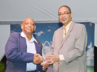 Mr Daniel Henry (left) receives the Environmental Excellence Award from a director of the St. Kitts Tourism Authority, Mr A.U. Brown. (Picture courtesy Willett's Photo Studio)