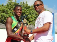 Deputy Premier of Nevis and Minister of Youth and Sports on Nevis Hon. Mark Brantley presents trophy to young Charlestown triathlete Romel Gaskin, after he arrived 4th at the finish line. He was the first Nevisian to finish the MaccaX Nevis International Triathlon on November 16, 2013