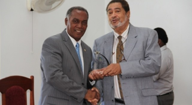 Premier of Nevis Hon. Vance Amory (l) receiving a plaque from Deputy Governor General His Honour Eustace John from the Nevis Island Assembly as one of the longest serving parliamentarian at a special sitting of the Assembly on December 10, 2013 at the at its Chambers in Hamilton House