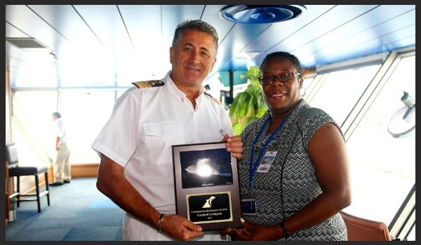 Acting Chief Executive Officer, Carolyn James, commemorates the inaugural visit of the Carnival Conquest with a plaque exchange with the Captain.