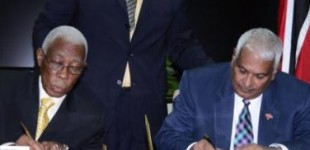 Minister of Foreign Affairs and Foreign Trade, Senator A.J. Nicholson (left), and Trinidad and Tobago's Minister of Foreign Affairs, Winston Dookeran, sign an agreement outlining the path to be taken in improving free trade and free movement arrangements between the two countries. JIS photo