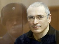 Jailed Russian former oil tycoon Mikhail Khodorkovsky stands in the defendants' cage before the start of a court session in Moscow December 28, 2010. REUTERS/Tatiana Makeyeva