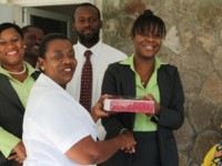 President of the Bank of Nevis Social Club Marva Walwyn (extreme right), presents gifts to Assistant Manager at the Flamboyant Nursing Home Nurse Ima Stanley while Vice President Mr. Regis Wiltshire (back row middle) and other members of the Bank of Nevis look on
