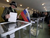 A woman holds a Russian flag as she casts her ballot during the referendum on the status of Ukraine's Crimea region at a polling station in Bakhchisaray March 16, 2014. Crimeans decided on Sunday whether to break away from Ukraine and join Russia in a referendum that has alarmed the ex-Soviet republic and triggered the worst crisis in East-West relations since the Cold War.  REUTERS/Sergei Karpukhin (UKRAINE  - Tags: POLITICS CIVIL UNREST ELECTIONS)