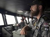Leading Seaman Luke Horsburgh stands watch during his duty as Quartermaster on the bridge of the Australian Navy ship HMAS Success after it arrived in the search area for missing Malaysian Airlines flight MH370 in this picture released by the Australian Defence Force on March 23, 2014. Australia's prime minister said on Sunday there was