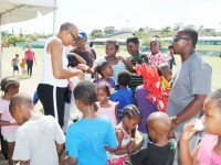 Children receiving Easter eggs from the Hon Marcella Liburd.
