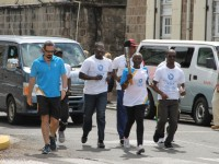 Athetes help to carry the Queen's Baton around the island of Nevis on March 29, 2014