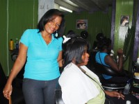 Ms Altagracia with a client at her beauty salon on Cayon Street in Basseterre's Central Business District.