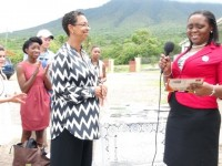 (L-R) University of Virginia Representative Dr Jeanita Richardson presents some books and school supplies to Education Officer and Language Arts Coordinator in the Department of Education on Nevis Avril Elliott on behalf of the Ivor Walters Primary School during a brief ceremony at the school's compound on May 27, 2014, while students of the University look on