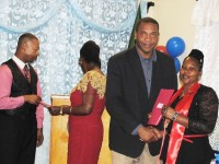 Hon. Glenn Phillips presents a certificate to one of the graduates, Ms. Janice Lake. In the background are PEP's Pastor Keith Warner, and PEP's Programme Officer (Monitoring and Evaluations) Mrs. Beverley Williams.