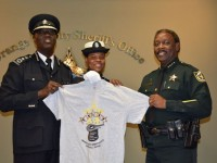 Sgt. Lyndita Powell and Commissioner Walwyn accepts t-shirt from Sheriff Demings