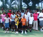 Chris Myrold  in red and white and Anthony Webbe in black and white with children at Tennis program