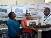 Mrs. Samaroo (accepting on behalf of her husband) accepting his prize from Mr. Laughton Herbert. Also in the photo is Ms. Jonelle Rawlins Drew, Client Relations and Marketing Manager