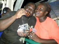 Vendor Idela Pemberton poses with a patron as he enjoys a chicken wing -
