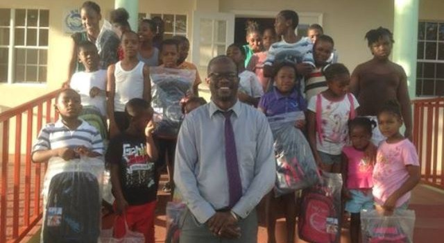 Hon. Patrice Nisbett with students receiving their school bags and supplies in front of the Barnes Ghaut Community center.