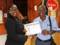 """Deputy Post Mistress General Rhonda Forbes-Williams presents """"Postman of the Year"""" award for 2014 to Vernon """"Tim"""" Wilkinson at the Post Office in Charlestown"""