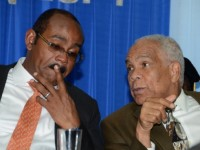 Prime Minister of Antigua and Barbuda and CARICOM Chairman, Hon. Gaston A. Browne (left), listens keenly to Minister of Transport, Works and Housing, Dr. the Hon. Omar Davies (right), at the Caribbean Maritime Institute's 33rd annual graduation ceremony, held at the Jamaica Conference Centre on November 13. Prime Minister Browne was the guest speaker.
