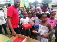 Mr. Cory Tyson (Red shirt looking in camera) with children at his back to school event