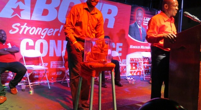 Election Bell is settled on the pedestal by Mr. Konris Maynard at the Lime Kiln Meeting in West Basseterre on January 18th 2015 as Prime Minister the Rt. Hon. Dr. Denzil L. Douglas speaks at the podium.