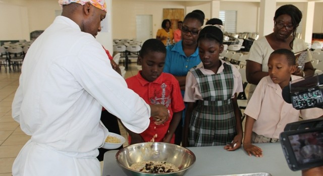Students of the Charlestown Primary School look on at a Mini Chief Academy session as Celebrity Chief of Atlanta Marvin Woods demonstrates how to make healthy snacks at the school's kitchen on February 24, 2015