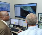Prime Minister Harris views a demonstration of advanced security technologies at the Emergency Operation Center of Ross University.