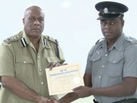 Constable Ronrick Huggins accepts certificate of completion from Acting Commissioner of Police Stafford Liburd