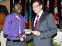 CDB President Dr. Warren Smith presents award to James Galloway. (Media credit: SKNIS)
