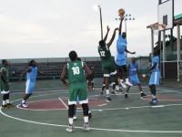 Development Bank Challengers Exodus player Jamal Sutton (no. 12) beats a block by Cotton Ground Rebels player Justin Jeffers during their SKNABA Premier League game on Saturday July 11 at the Grell Hull-Stevens Netball Complex in Stoney Grove. In guard is Javier Sutton (no. 10).