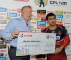 PORT OF SPAIN, TRINIDAD - JULY 25:  KAMRAN AKMAL (R) of Trinidad & Tobago Red Steel receives the Hero cheque at the end of a Semifinal match between Trinidad & Tobago Red Steel and Guyana Amazon Warriors as part of week 5 of the Caribbean Premier League 2015 at Queens Park Oval on July 25, 2015 in Port of Spain, Trinrdad.  (Photo by Randy Brooks/CPL)