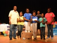 (l-r) 3rd place winner Elizabeth Pemberton Primary's Denzil and D'Rhys Stanley, Family Book Feud 2015 winners Charlestown Secondary's Shenel Nisbett and Shevonel Williams, Principal Education Officer in the Department of Education Palsy Wilkin and 2nd place winner Montessori Academy's Casandra and Lincoln Sandiford, at the end of the 6th annual joint School Libraries and Department of Education's Warner's One Stop Family Book Feud on July 11, 2015, at the Nevis Performing Arts Center