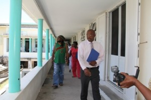 """Surgeon at the Alexandra Hospital Dr. Cardell """"Bal"""" Rawlins leading the tour of the Alexandra Hospital with international reggae artistes, members of Tender Care International hosts of a benefit concert for health facilities on Nevis, Deputy Premier and Minister of Health Hon Mark Brantley and other members of the Nevis Island Administration"""
