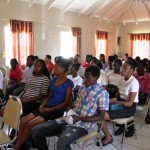 The 44 interns listen attentively at the closing ceremony of the Ministry of Social Development Youth Affairs Division's 10th Annual Summer Job Attachment Programme at the Red Cross conference room in Charlestown