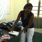Nevisian Association of Washington DC representative Mrs. Susan Clarke hands over school supplies donated by the association to the NIA's Department of Education