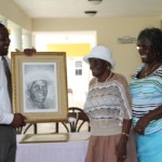 St. Thomas' Parish's eldest resident Alice Nisbett accepts her self portrait from the Permanent Secretary in the Ministry of Social Development Keith Glasgow on United Nations International Day of Older Persons on October 1, 2013, while her daughter Muriel St. Jean looks on.