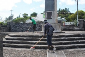 PEP is not just about cutting grass: They also keep national monuments clean. Two of PEP workers are seen at work at the War Memorial in Basseterre.