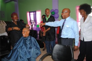 Light moment as PEP Cosmetology course facilitator, Ms Juliette Queeley (left) mockingly attempts to cut Hon Marcella Liburd's nonexistent hair. Amused are, from right, PEP Cosmetology course facilitator Mrs Amoy Arache, Deputy Prime Minister the Hon Dr Earl Asim Martin, and PEP Project Manager Mr Geoffrey Hanley.