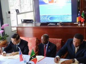 Minister of Information Technology, the Hon. Glen Phillip (right) and Taiwan's Resident Ambassador, His Excellency Mr. Miguel Tsao (left) sign the Agreement in the presence of St. Kitts and Nevis' Prime Minister the Right Hon. Dr. Denzil L. Douglas (c).