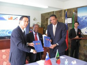 Minister of Information Technology, the Hon. Glen Phillip (right) and Taiwan's Resident Ambassador, His Excellency Mr. Miguel Tsao (left) exchange copies of the new ICT Agreement in the presence of St. Kitts and Nevis' Prime Minister the Right Hon. Dr. Denzil L. Douglas (c).