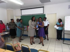 Vice President of the new Nevis National Women's Council Mrs. Vernie Amory receives a token from Assistant Secretary in the Ministry of Social Development Ms. Michelle Liburd while other members of the Council look on