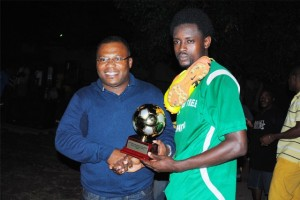 National Caribbean Insurance Ltd representative Mr Floyd Charles presents a trophy to Randy Thomas of the Glen 'Ghost' Half Way Tree United FC, that will be on display at the sponsor's office.