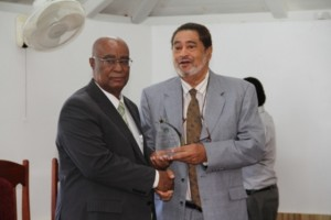 Leader of the Opposition Hon. Joseph Parry (l) receiving a plaque from Deputy Governor General His Honour Eustace John from the Nevis Island Assembly as one of the longest serving parliamentarian at a special sitting of the Assembly on December 10, 2013 at the at its Chambers in Hamilton House