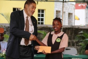 Deputy Governor General His Honour Eustace John presents Alexander Hamilton Scholarship package to Ms. Shadae Stanley of the Gingerland Secondary School