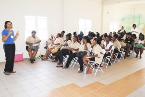 Mrs Natalie Fough of the St. Kitts and Nevis Red Cross Society, and listening to her are cosmetology trainees.