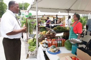 General Manager of the Development Bank of St. Kitts and Nevis Mr Lenworth Harris with Mrs Emontine Thompson at her booth at a Customer Appreciation Bazaar hosted by the Development Bank in Charlestown as part of its 30th anniversary celebration in May 2011.