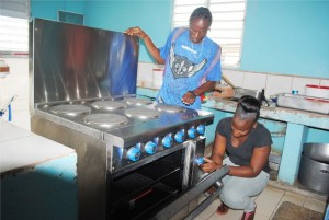 PEP trainees Jamal Pemberton and Nakita James checking to ensure that the cooker at the Cardin Home is in working condition.