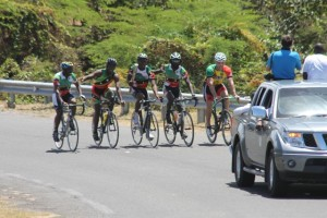 Members of the Nevis Cycle & Triathlon Club help to carry the Queen's Baton around the island of Nevis on March 29, 2014