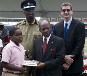 PM Douglas flanked by COP Walwyn and Sean McCormack presents a gift to a MAGIC graduate