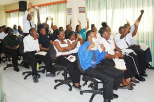 Graduates of the Island Constable Training No. 1/2014 cheer as Deputy Commandant Police Training School, Inspector Eldrin Dickenson relayed the ceremony via a live Skype link to one of their instructors Woman Sergeant Shorna Edwards, who was in El Salvador for training.
